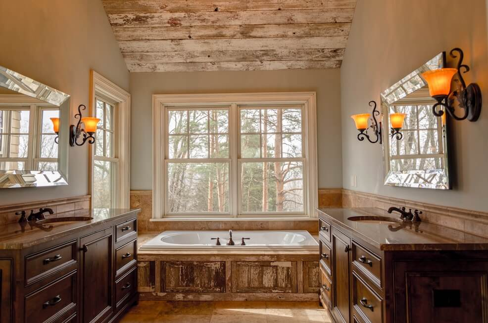 Rustic bathroom with bathtub in front of large window